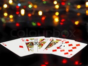2204708-dice-and-playing-cards-poker-royal-flesh-on-back-background-casino-lights